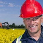 A royalty free image from the oil industry of an oil worker in front of pumpjacks and a canola field